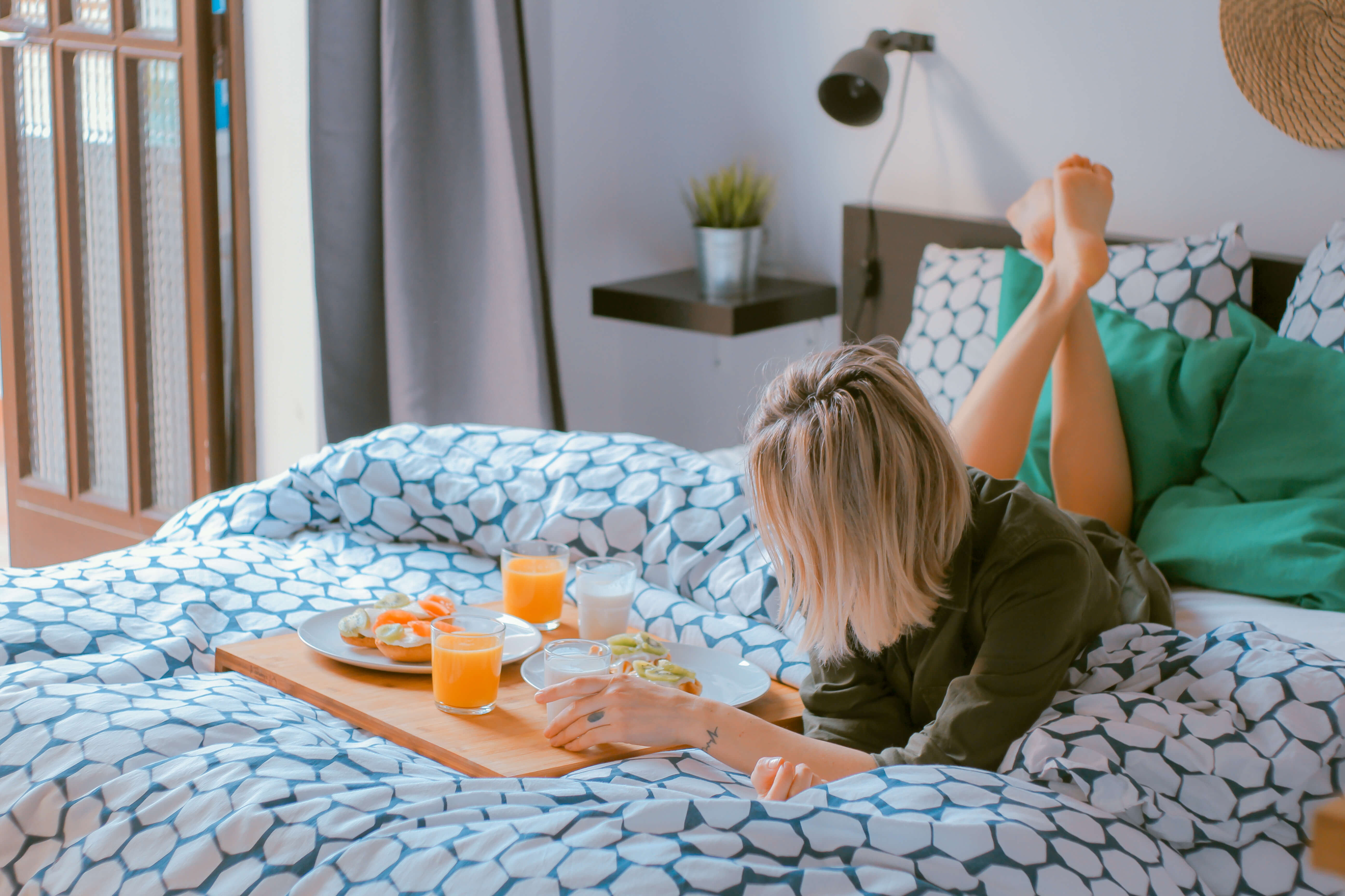 Girl laying on a bed with breakfast